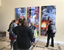 A handful of people look at an NIA collage on the wall.