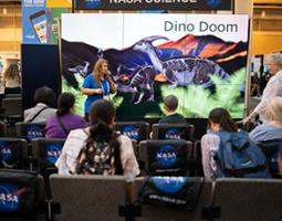 """A woman stands in front of a wall of screens reading """"Dino Doom""""."""