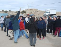 A group of people stand outside on the pavement in front of rocky hills