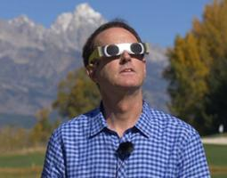 A man wearing glasses designed for safely viewing the eclipse