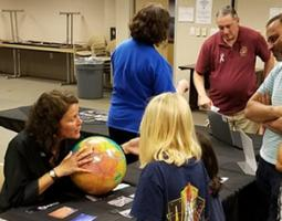 A woman holds a globe in front of children.