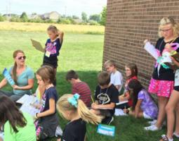 Female teacher and fourth graders sitting on the grass and reading