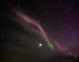 STEVE (Strong Thermal Emission Velocity Enhancement) is seen as a thin purple ribbon of light.