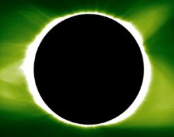 Total solar eclipse against against a light and dark green sky.