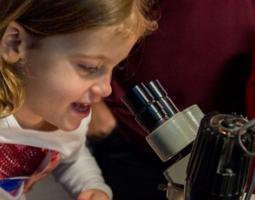 A little girl looks through a telescope
