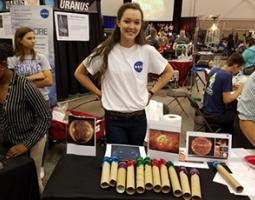 A female high school student in a NASA t-shirt stands behind a table with a sun exhibit