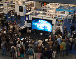 Photo of crowd watching video presentation on large Hyperwall screen
