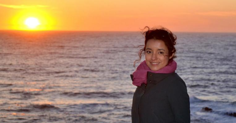 Photograph of woman standing in front of sun setting over large body of water