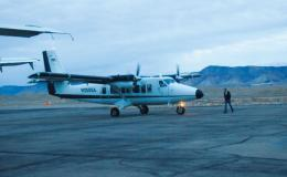 Photograph of small airplane on tarmac with mountains in the background.
